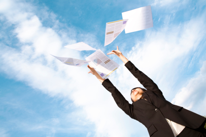 Businesswoman throwing her paperwork in the air
