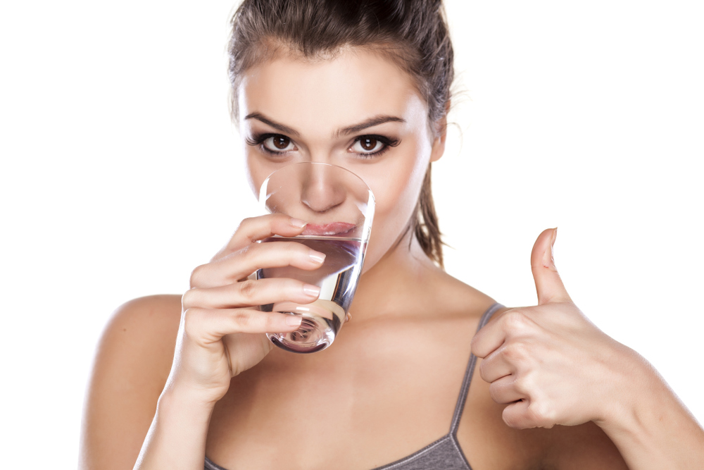 Woman Drinking Water Gives Thumbs up