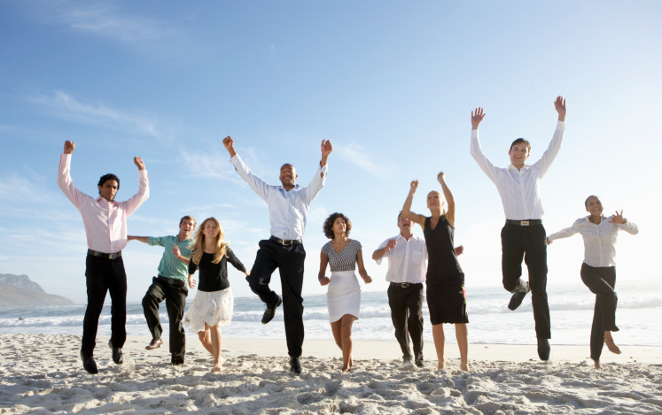 business people jumping on beach