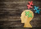 man with jigsaw pieces around head