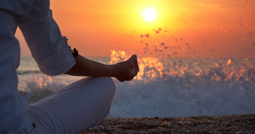 Woman meditating watching sunset