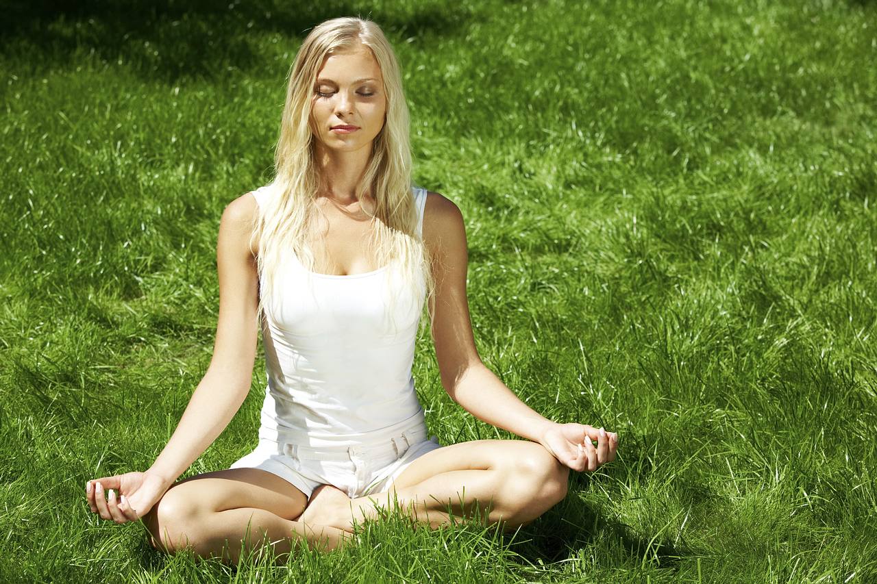 Meditating girl seated in lotus pose on green grass